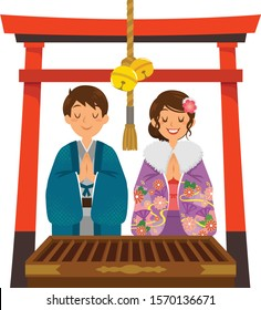Hatsumode tradition Japan. Young Japanese couple wearing kimono praying in a shrine under a red torii gate on New Year.