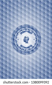 head with gears inside icon inside blue badge with geometric pattern.