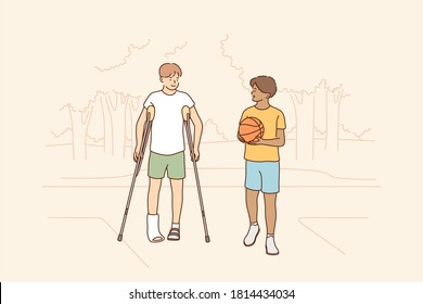 Health, care, sport, basketball, friendship concept. Young boys children african american guy holding ball and disabled friend with crutches walking together. Friendly support and rehabilitation.