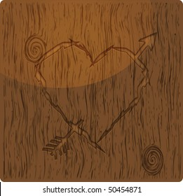 Heart shape with arrow carved into wood.