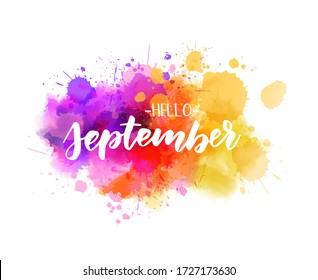 Hello September -  handwritten modern calligraphy lettering on abstract watercolor imitation splash. Purple, pink and yellow colored. Painted background.