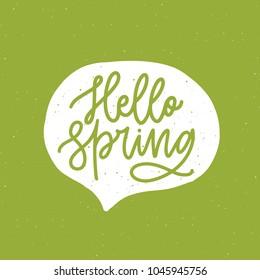 Hello Spring phrase handwritten with elegant cursive font or script inside speech balloon or bubble on green background. Springtime seasonal lettering or inscription. Hand drawn vector illustration.