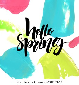 Hello spring text on colorful background with pink, green and blue brush strokes