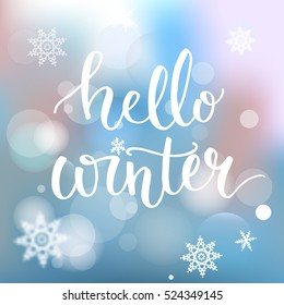 Hello winter banner. Brush calligraphy at blue winter background with snowflakes and bokeh lights. Vector card design with typography.