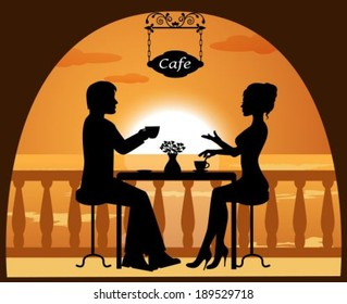 heterosexual couple in a cafe on the beach at sunset