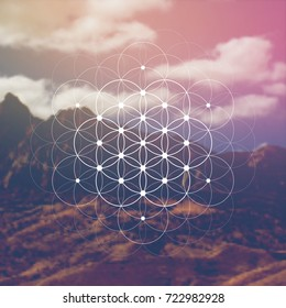 Hipster scientific illustration with flower of life - the interlocking circles ancient symbol in front of blurry photo background.