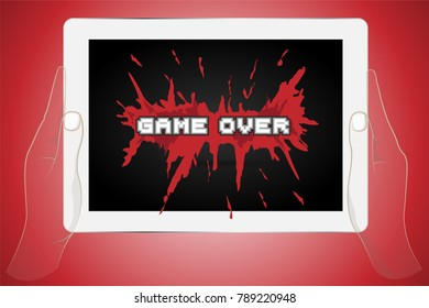 Holding tablet with Game Over splash screen. Computer Game.
