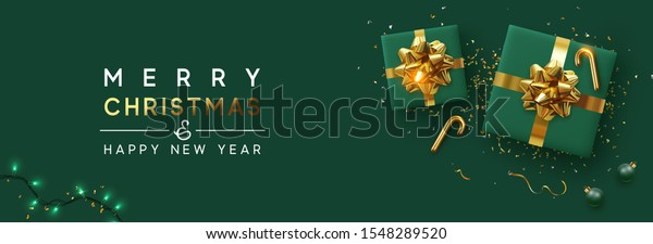Holiday background Merry Christmas and Happy New Year. Xmas design with realistic festive objects, sparkling lights garland, green gift box, ball bauble, glitter gold confetti. Horizontal banner