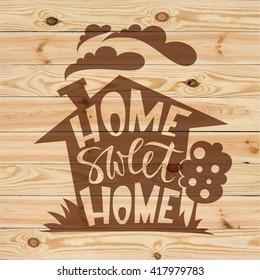 Home sweet home lettering on wood background. Modern brush pen hand lettering design.
