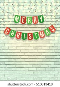 Homemade flag garland with Merry Christmas text on white brick wall with lights and snow. LED Light Glowing bulbs. Template for congratulation, banners, flyers and greeting card.
