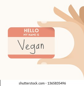 Human hand holding card with text Hello, I am Vegan. Concepts: healthy vegetarian eating lifestyle, fruits and vegetables diet, health and medicine, natural nutritions etc, nonviolence etc.