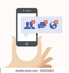 Human hand holding mobile phone with social network notification on screen