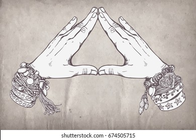 Human hands make triangle shape isolate on white background. Illuminati sign. Sacred geometry. Religion, spirituality, occultism, alchemy magic. Vintage boho style accessories with hippie bracelets.