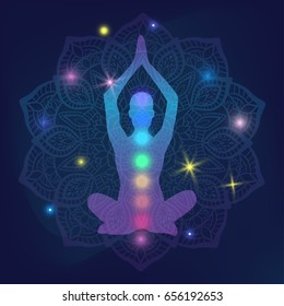 Human silhouette meditating or doing yoga with rainbow lights of Chakras inside on shiny mystic galaxy background with glowing stars and mandala from the deep cosmic night space for yoga studio logo