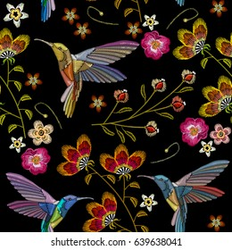Humming bird and tropical flowers embroidery seamless pattern. Beautiful hummingbirds and exotic flowers embroidery on black background. Template for clothes, textiles, t-shirt design