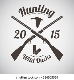 Hunting Vintage Emblem. Cross Hunting Gun With Ammo and Flying Duck Silhouette. Suitable for Advertising, Hunt Equipment, Club And Other Use. Dark Brown Retro Style.  Vector Illustration.