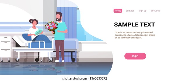 husband holding flowers bouquet for his wife with newborn baby sitting on bed father visiting new born child happy family parenthood concept hospital ward interior horizontal copy space