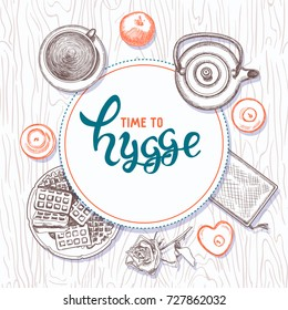 Hygge is a Danish living style. Vector background with hand drawn illustrations cozy home things: candles, teapot, cup with tea and waffle, apples on wooden texture. Lettering time to hygge.