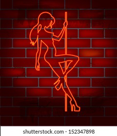 An illuminated neon sign for a strip club mounted on a brick wall