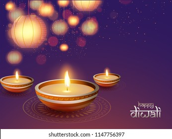 Illuminated oil lamps (Diya) on shiny background decorated with hanging paper lanterns (lamps) and blurred lighting effect for Diwali festival celebration.