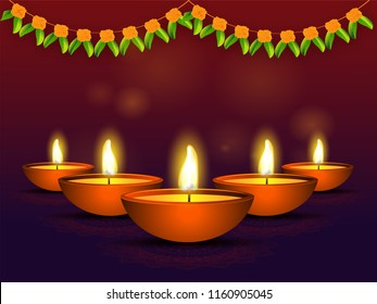 Illuminated oil lamps on shiny brown background decorated with floral garland (Toran) for Diwali Festival celebration.