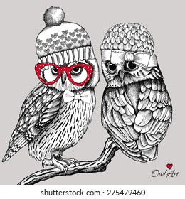 Image of two owls in knitted hats, glasses on a branch. Vector illustration.