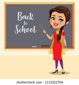 Indian school teacher wearing a salwar kameez outfit in front of a blackboard
