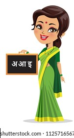 Indian school teacher wearing a saree and holding a slate with hindi/ marathi alphabets written on the slate