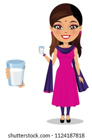 Indian woman wearing a salwar kameez is holding a glass of milk in her hand