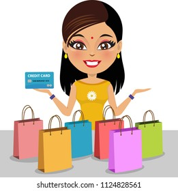 Indian woman wearing a salwar kameez is holding a credit/ debit card in her hand. She has shopped a lot and there are shopping bags in front of her