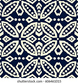 Indigo dye batik geometric ornament, ethnic motif with rings and rhomboid shapes. Ecru on blue background. Textile print.