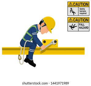An industrial worker with safety harness is working at height