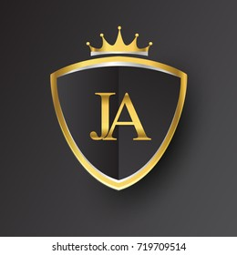 Initial logo letter JA with shield and crown Icon golden color isolated on black background.