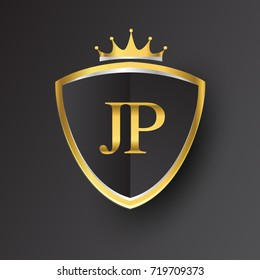 Initial logo letter JP with shield and crown Icon golden color isolated on black background.