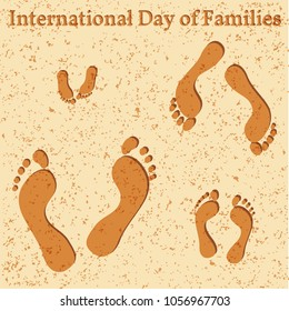 International Day of Families. Concept of a family of 4 people - father, mother, daughter, baby - their footprints on the beach