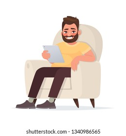 Internet addiction. A waste of time on social networks. A man holds a tablet sitting on the couch. Vector illustration in cartoon style