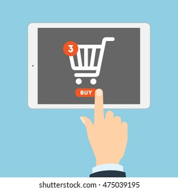 Internet shopping concept. Hand pulling buy button on tablet. Three items in shopping cart. E-commerce concept. Shopping online.