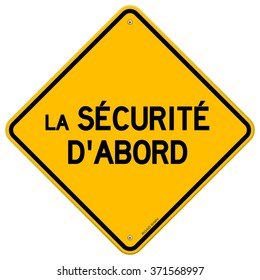 Isolated single yellow diamond shaped la securite d'abord hazard sign over white background - in English saying Safety First