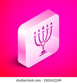 Isometric Hanukkah menorah icon isolated on pink background. Hanukkah traditional symbol. Holiday religion, jewish festival of Lights. Silver square button. Vector Illustration