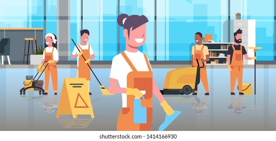 Janitors team cleaning service concept. Cleaners team in uniform working together with professional equipment. Modern co-working center office interior.  Flat full length horizontal.