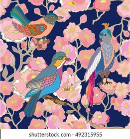 Japanese garden. Seamless oriental pattern with Victorian motifs. Blooming cherry flowers and paradise birds. Vintage textile collection. Colorful on dark blue.