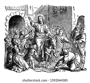 Jesus riding on colt and raising right hand, crowd of people with palm branches welcoming him and a man laying cloth on ground for colt to walk on, vintage line drawing or engraving illustration