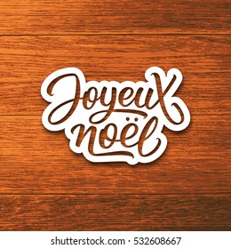 Joyeux Noel text on paper label with hand lettering over wood background. Merry Christmas sticker or greeting card vector design template with french inscription