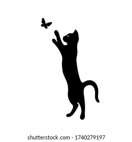 A kitten plays with a flying butterfly. Black silhouette of a cat isolated on white background. The symbol of Halloween. Can be used as a sticker template, logo element, icon for web design.