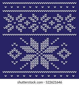 Knitted pattern in the form of white snowflakes on a dark blue background. The classic pattern for sweaters, mittens, scarves and warm socks.