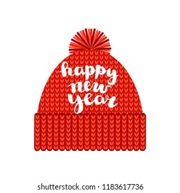 """a knitted red cap with a pompom with the inscription """"Happy new year"""". Isolated on a white background. Autumn or winter seasonal accessory isolated on white background."""