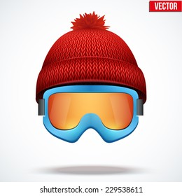Knitted woolen red cap with snow ski goggles. Winter seasonal sport hat. Vector illustration isolated on white background.