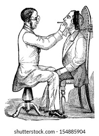 Laryngoscopy, showing a doctor looking into a patient's mouth, illuminated by indirect light from a gas lamp, vintage engraved illustration. Usual Medicine Dictionary by Dr Labarthe - 1885