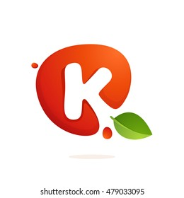 Letter K logo in fresh juice splash with green leaves. Vector elements for natural application, ecology presentation, business card or cafe posters.