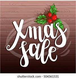 """Lettering """"Xmas Sale"""" and hand drawn Christmas Holly Berry on a wooden background. Template for greeting cards, invitations, posters, flyers. Vector illustration."""